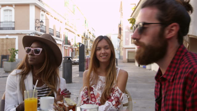 Handheld panning shot of friends at a table outside a cafe, shot on R3D video