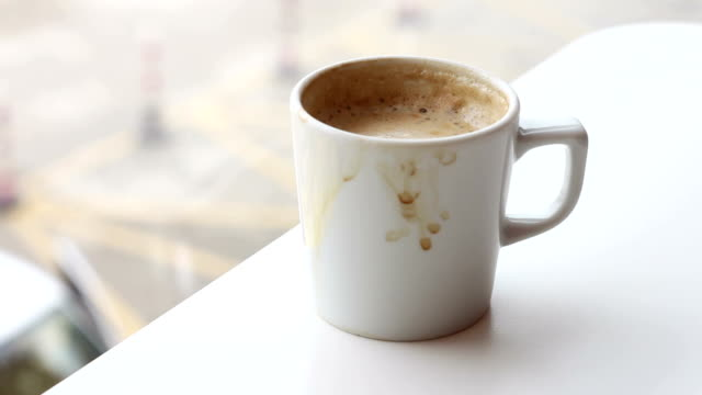 Handheld shaky shot of coffee mug on a cafe table with coffee drops on it video