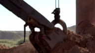 Handheld shot of excavator bucket mixing ore at a crushing and sorting factory. video