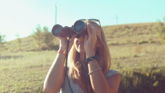 Handheld shot of girl looking with binoculars video
