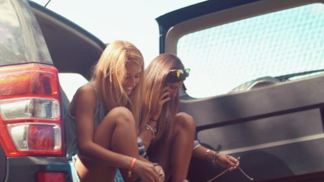 Handheld shot of hikers sitting in car trunk video