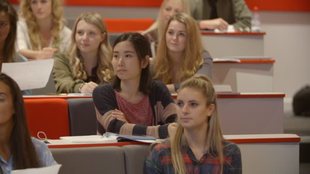 Handheld tilt shot of students in university lecture theatre video