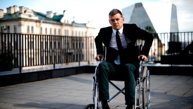 Handicapped businessman trying to get up from wheelchair outdoor video
