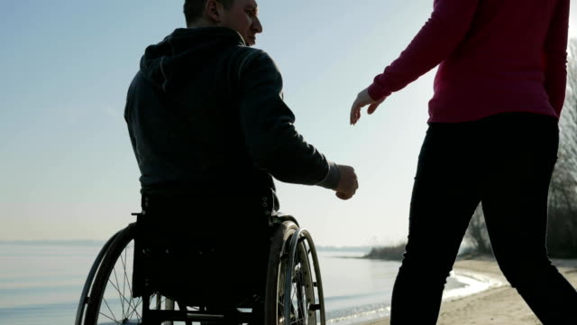 handicapped love, invalid person on wheel chair with girl, couple of video