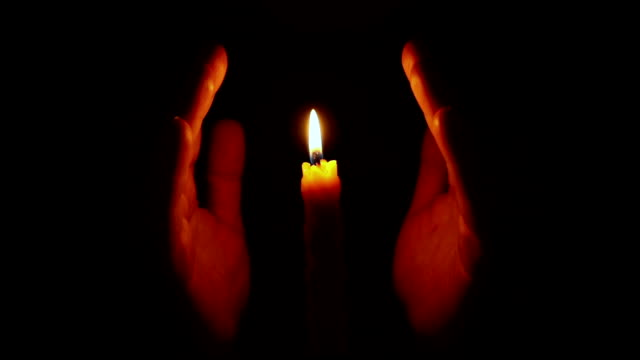 Hands approaching burning candle video