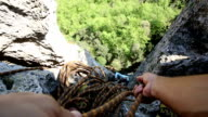 POV of hands belaying woman climber up steep rock video