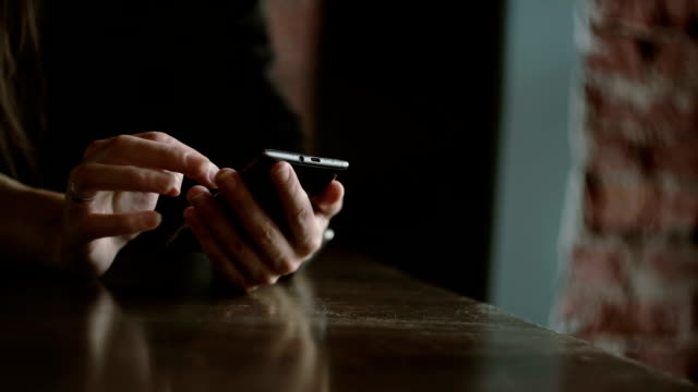 Hands closeup. Woman using her smartphon touchscreen device in loft cafe FullHD video