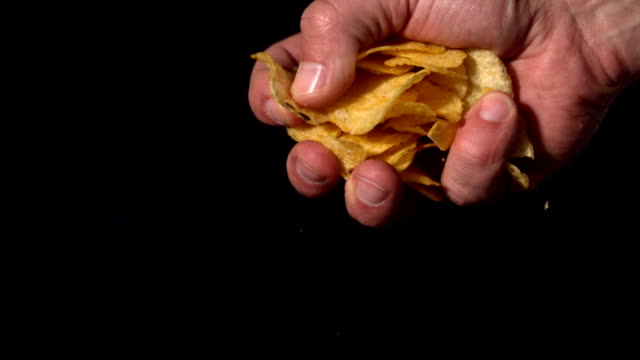 Hands crushing potato chips on black background video