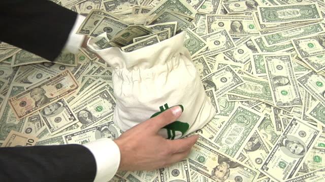 Hands grab a bag of money video