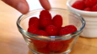 Hands grab raspberries out of clear bowl video