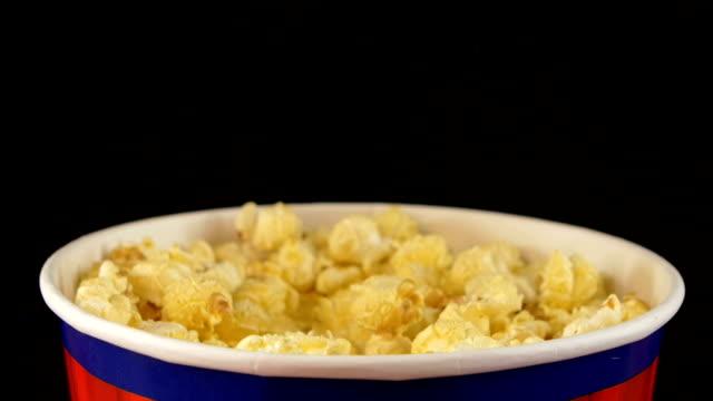 Hands grabbing popcorn on black, rotation video