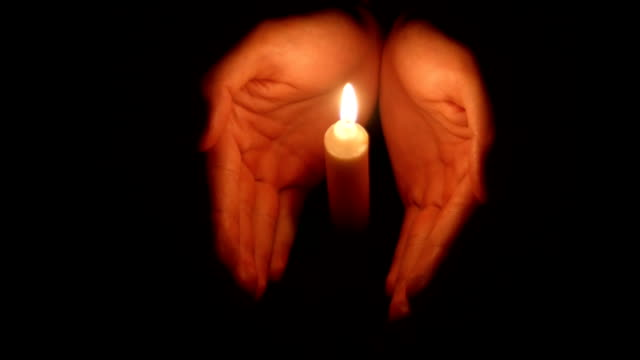 hands holding a burning candle in dark video