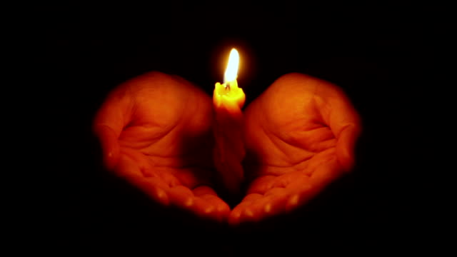 Hands holding burning candle video