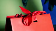 Hands in gloves untie a red ribbon of a luxury gift bag video