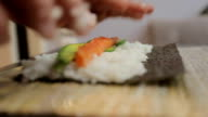 Hands make long sushi roll. Rice with pieces of fish. Sushi chef demonstrating skill. Famous japanese dish. video