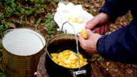Hands of a man close up, cut potatoes in outdoor video
