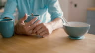 hands of a man playing with his wedding ring at the kitchen table. Slow motion video