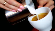 hands of barista making latte or cappuccino coffee pouring milk making latte art. video