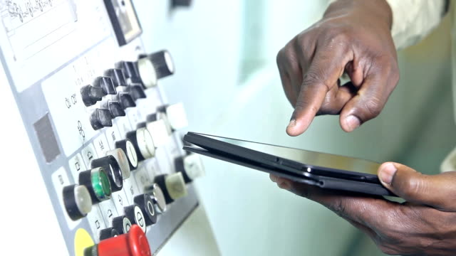 Hands of black man at control panel with digital tablet video