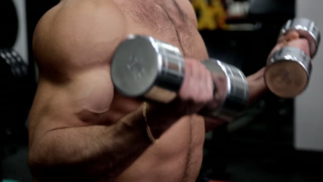 Hands of bodybuilder working with weights in the gym video
