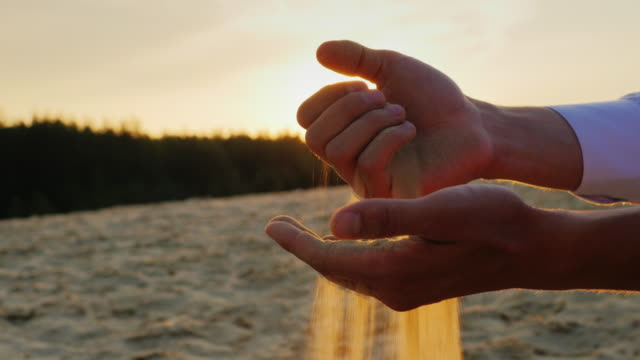 Hands of businessman man in a white shirt sifted sand through his fingers at sunset. The concept - a period of time, change video