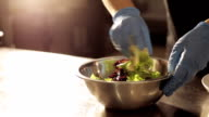 Hands of chef in gloves mixing lettuce with sauce in steel bowl. video