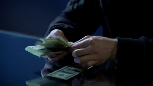 Hands of contract killer or bank robber counting money paid for committing crime video