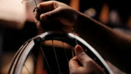 Hands of craftsperson repairing spokes on a bicycle wheel video