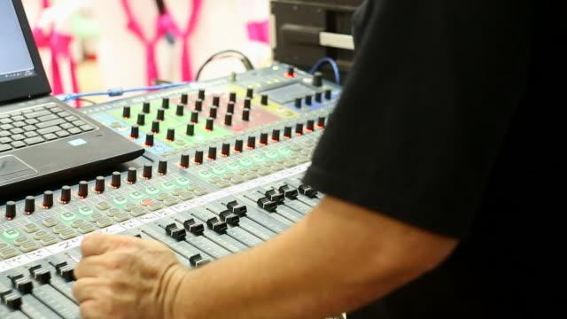 Hands of DJ tweak controls on record deck video