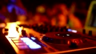 Hands of DJ tweak various track controls on dj's deck, camera is breathing video