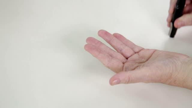 Hands of elderly woman pricking finger in insulin level test video