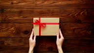 Hands of female placing a present box on a wooden background video
