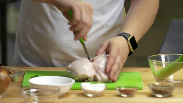Hands of male chef carve chiken on a cutting boardand dips into boiling water on kitchen video