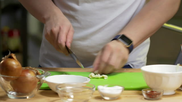 Hands of male chef slice garlic on a cutting board on kitchen video