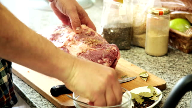 Hands of man add spices to the meat video