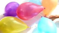 hands of man and woman flirting on bedsheets with colourful balloons around video