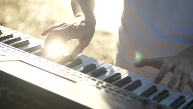 hands of men play on the synth. Man hands playing a MIDI controller keyboard synthesizer. Close up slowmotion video full hd video