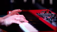 Hands of musician playing keyboard in concert video