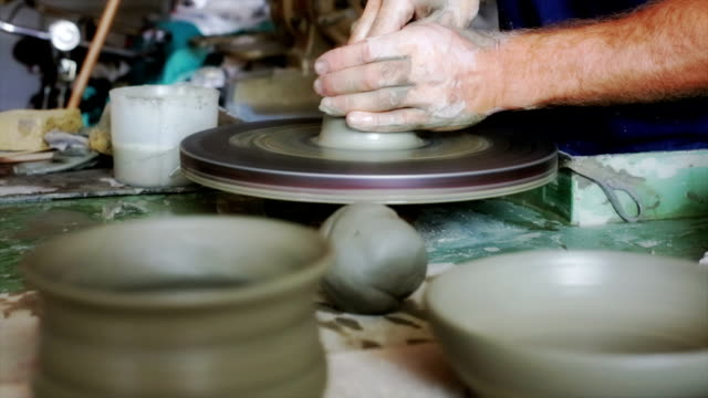 Hands of potter starting a clay pot video