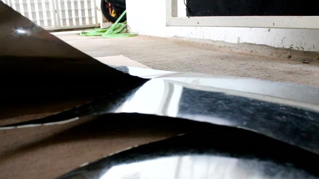 Hands of technician using hard scissor to cutting a sheet of alu zinc for circle layout shape video