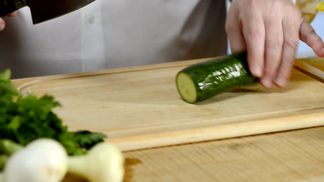 Hands of the cook knife big kitchen a fresh green cucumber on a chopping board from a tree video