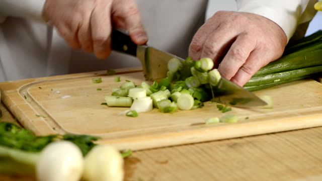 Hands of the cook knife big kitchen a fresh green feather onions on a chopping board from a tree video