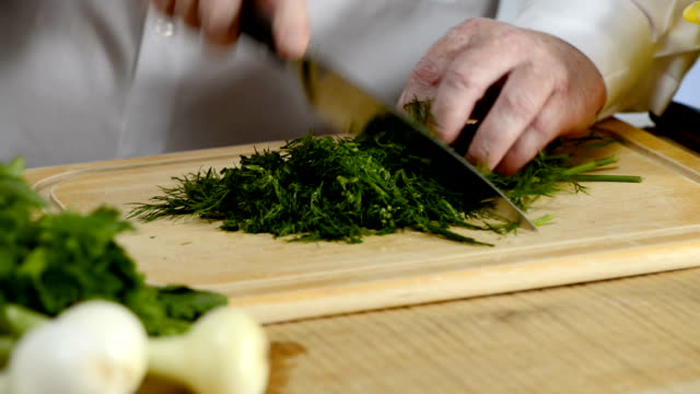 Hands of the cook knife big kitchen a fresh green fennel on a chopping board from a tree video