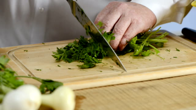 Hands of the cook knife big kitchen a fresh green parsley on a chopping board from a tree video