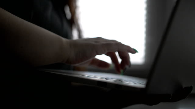 Hands of the girl, the brunette with long hair, with manicure printing the text on the laptop against the background of a window with blinds, the Close up video