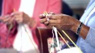 Hands of two senior women knitting video