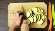 Hands of woman cutting eggplant on wooden board. view from above video