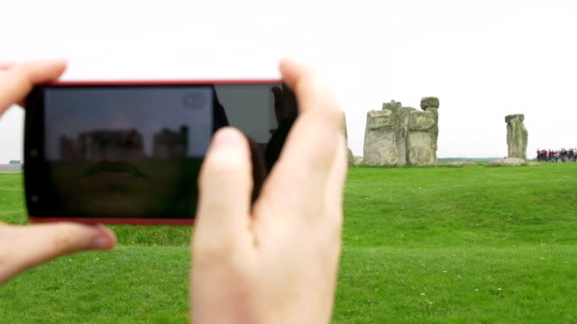 hands of woman holding a smartphone and making a picture to stonehenge video