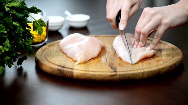 Hands of woman slicing raw fillets out of chicken breasts close-up video