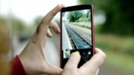 hands of woman using smartphone to make pictures of railtracks, railway video